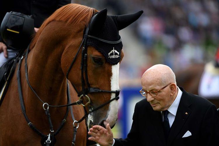 Hans Günter Winkler steht neben einem Pferd